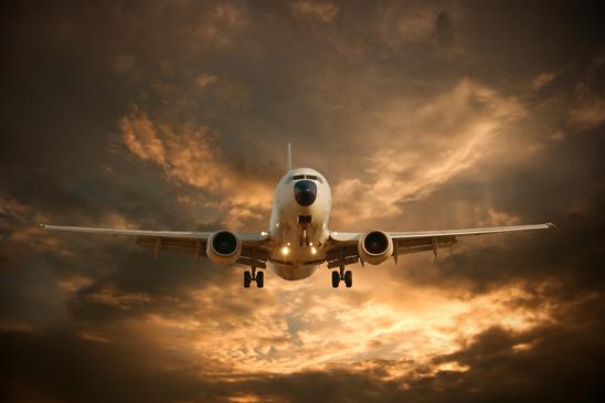 Landing airplane against glowing sky